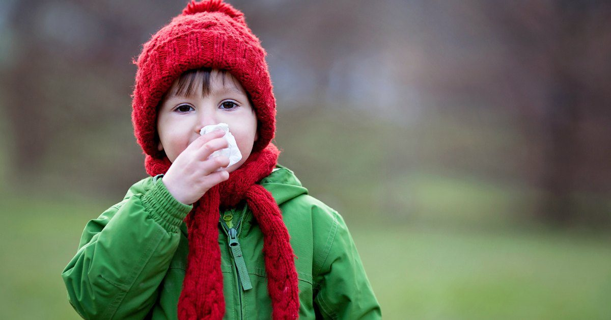 Boy outside wiping nose with Boogie Wipes® saline nose wipes